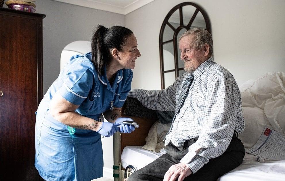 Community nurse, Danni, leaning towards a patient