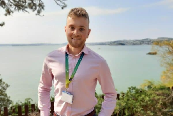 A photo of medicines optimisation pharmacist, Charlie, with the sea in the background